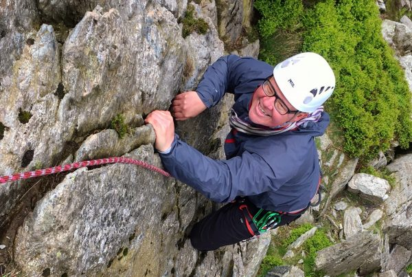 A climber grins as he makes a tricky move during a rock climbing course in Snowdonia