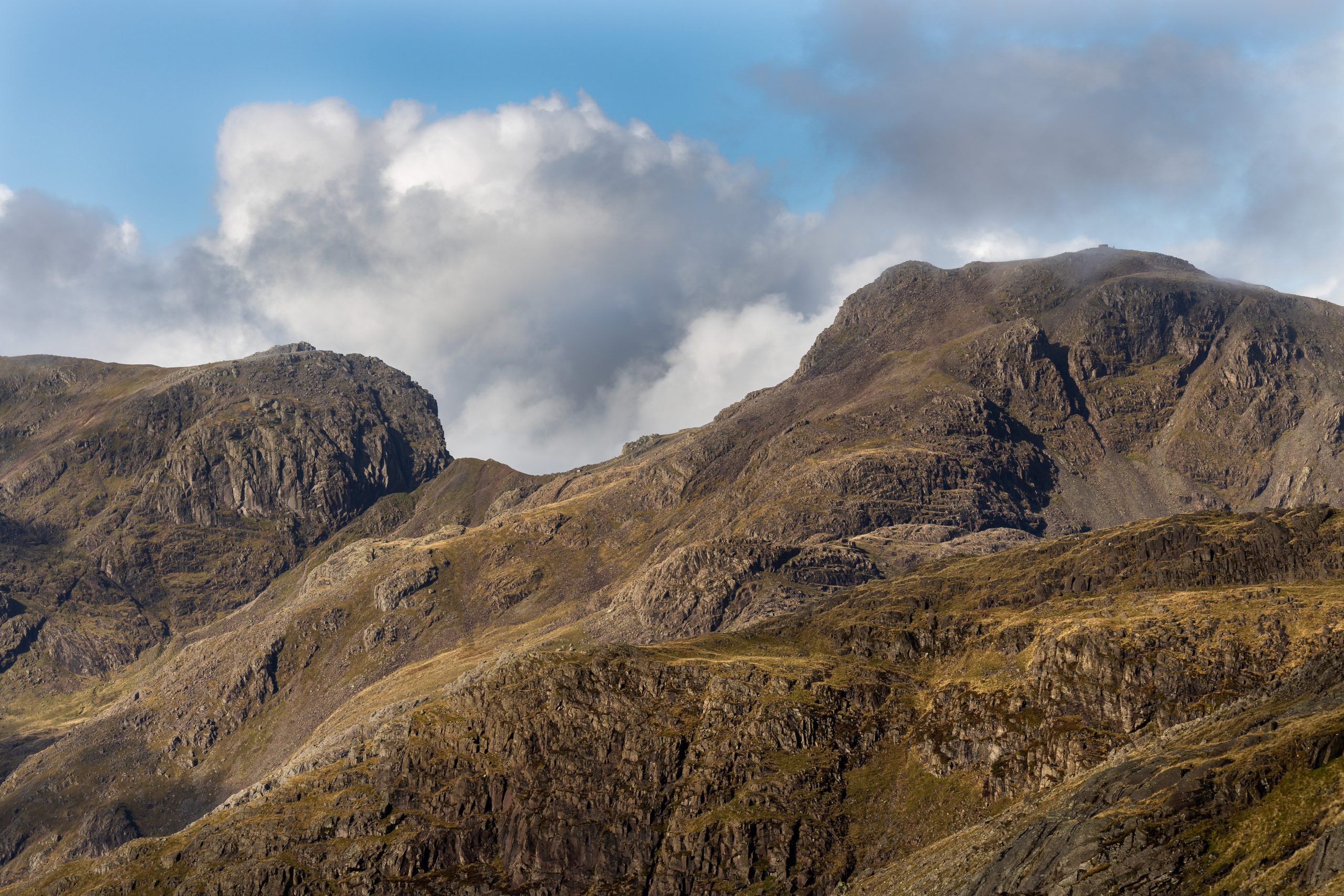 A close up of the cliffs of Scafell, with the col or saddle of Mickledore and Scafell Pike also visible on the right during a guided walk