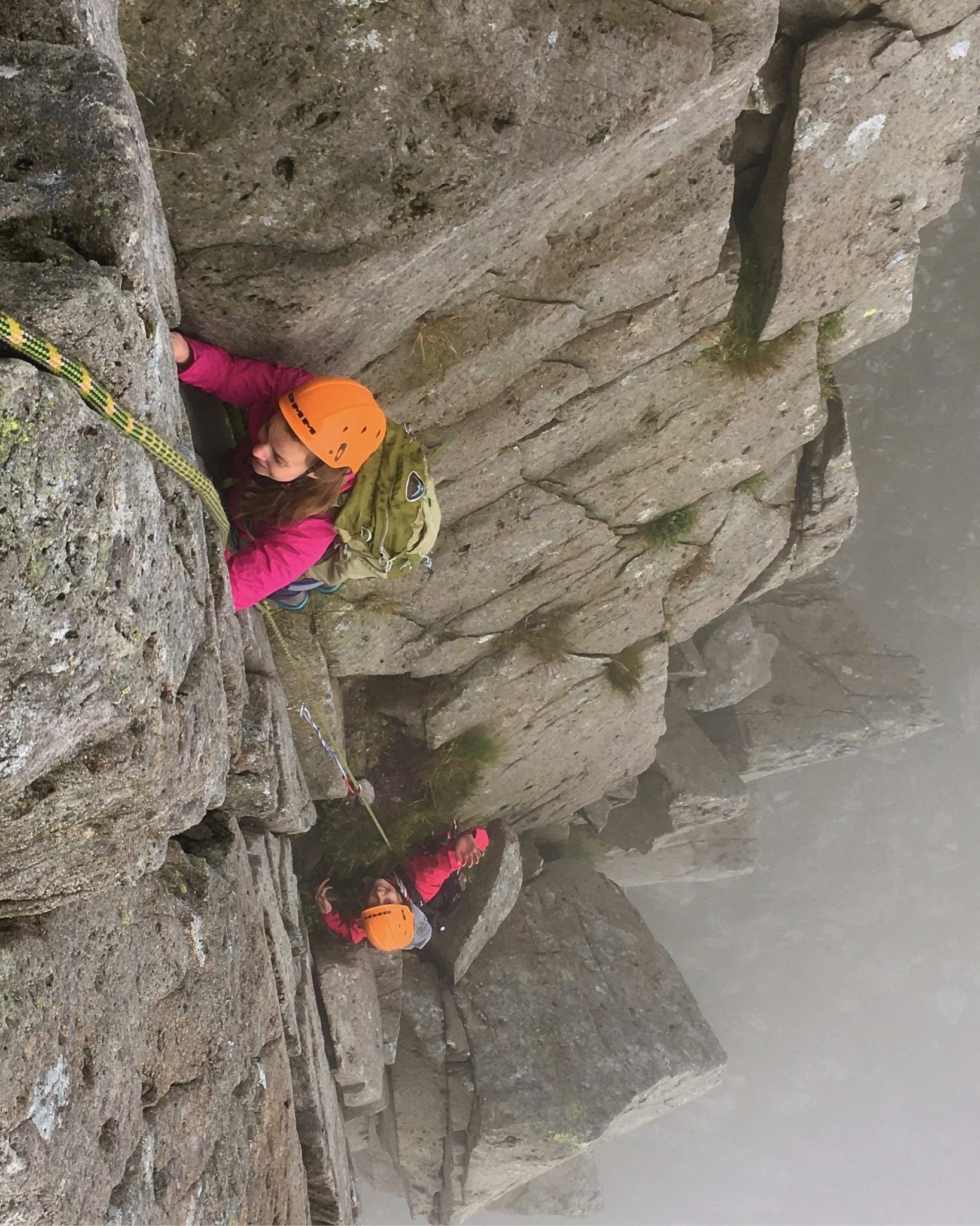 Two climbers tackling the difficult corner pitch high up on the Dolmen Ridge on Glyder Fach during an advanced scrambling course in Snowdonia
