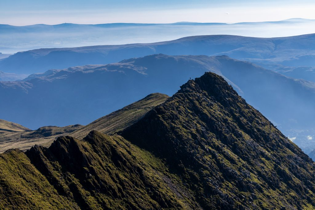 A single walker silhouetted in the early morning light on Striding Edge on Helvellyn during a guided walk in the Lake District