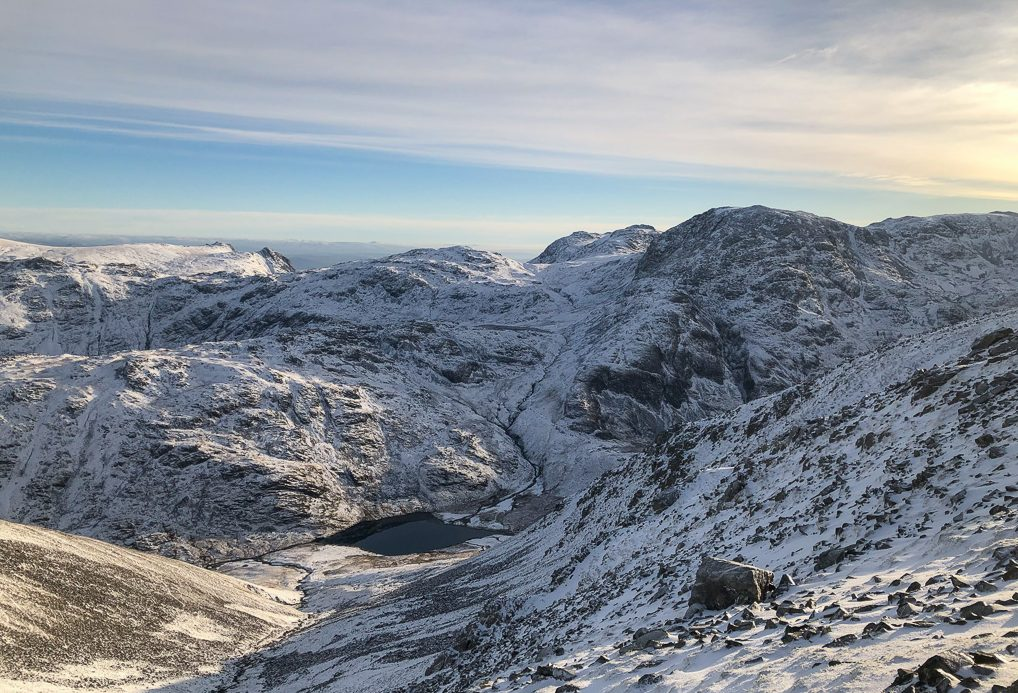 Styhead Tarn in the Lake District in winter. To its right is Great End and in the distance on the left the Langdale Pikes poke through.