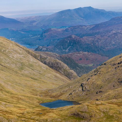 Looking over Styhead Tarn with Derwent Water and Blencathra visible in the distance