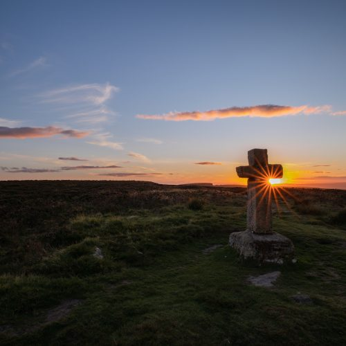 The sun setting behind Cowper's Cross on Ilkley Moor creating a sun burst effect, while walking in the Yorkshire Dales