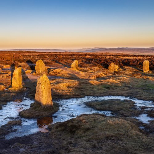 The Twelve Apostles stone circle on Ilkley Moor at dawn, with the view into Upper Wharfedale