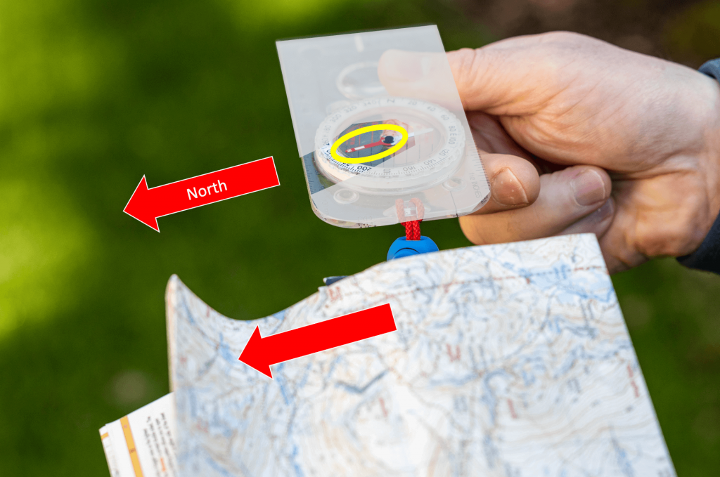 A compass being used to orientate a map by aligning the magnetic north needle with the top of the map
