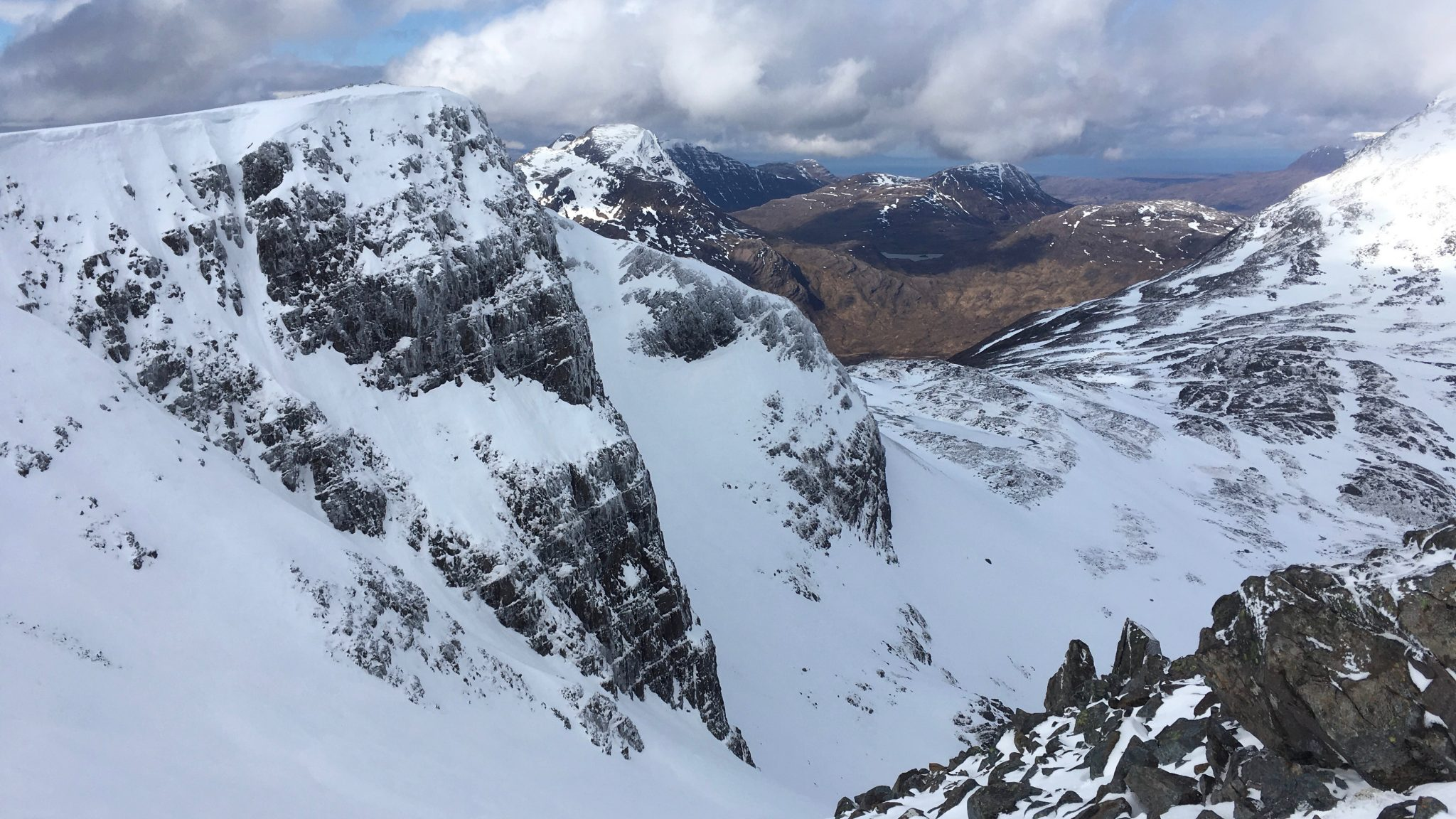 The view down a steep snow gully while out in the Scottish Highlands in winter practising winter navigation