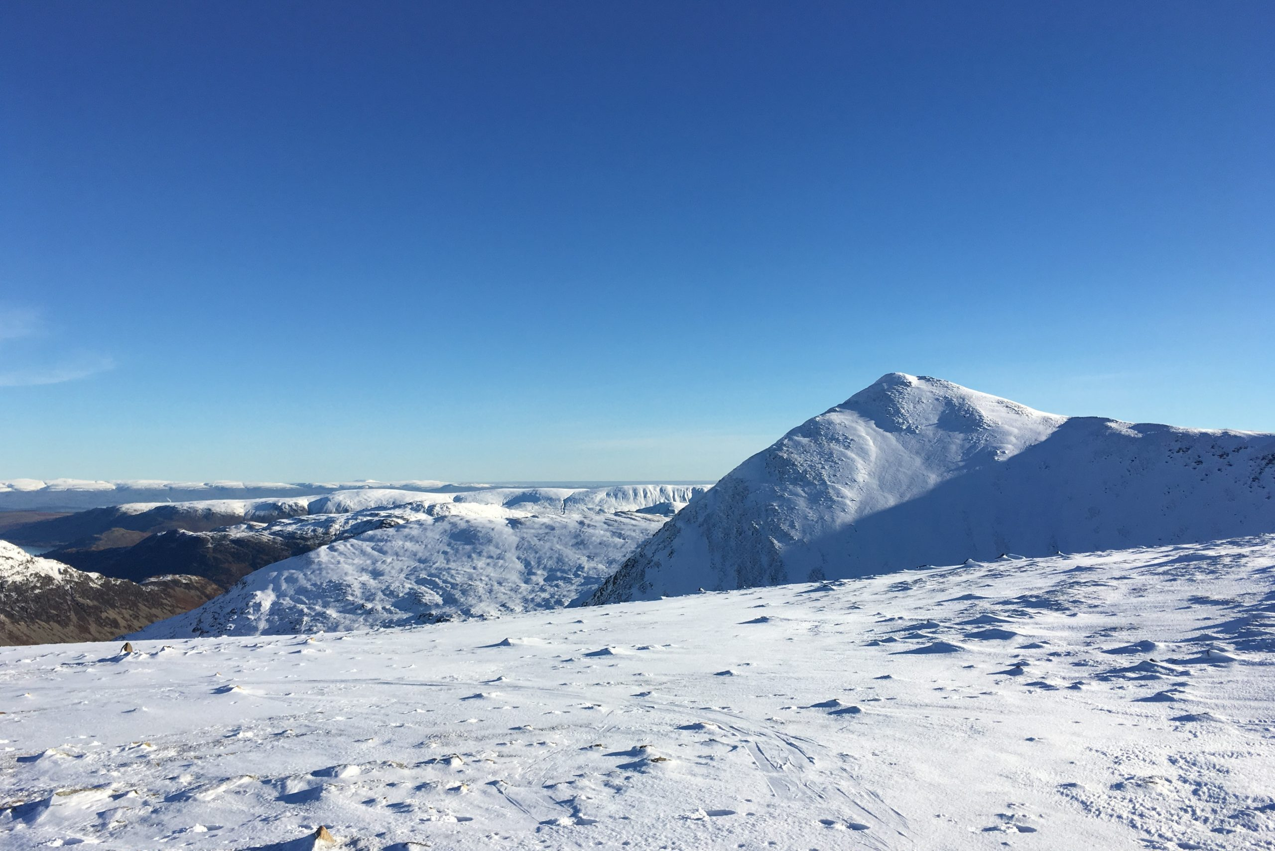 A snowy scene high up in the Lake District hills near Helvellyn during a winter skills course
