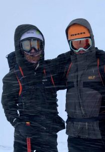 Two climbers wearing goggles huddle together for protection against the blizzard during a winter skills course in the Cairngorms