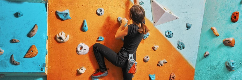 Climber on an indoor climbing wall, like our climbing courses in Leeds
