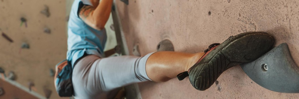 Climber placing their foot accurately, as we teach on our indoor climbing courses in Leeds