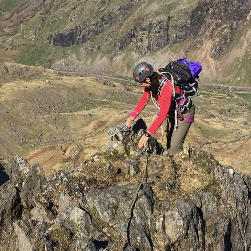 A mountaineer reaches the crest of the ridge of the Clogwyn y Person Arete with Llanberis Pass below during a summer mountaineering course in Snowdonia